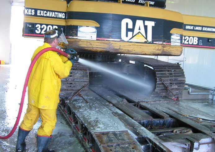 Mand iført gul dragt der vasker gravemaskine